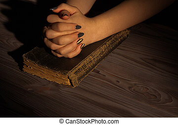 Woman's praying to God with folded hands on an old vintage holy bible.