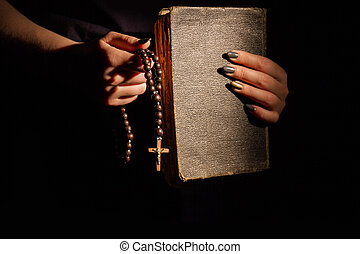 Woman's praying to God with rosary and bible.