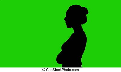 Woman's silhouette in profile with arms crossed on green background