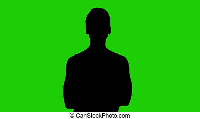 Woman's silhouette with arms crossed on green background
