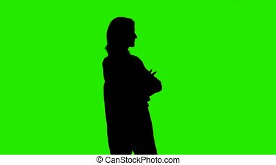 Woman's waiting silhouette in jacket with arms crossed on green background