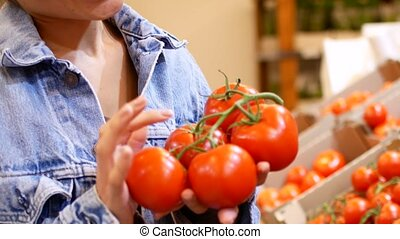 Woman's white hands take few colorful tomatoes in...