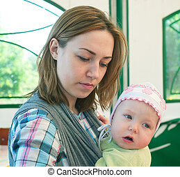 women and a little child in sling