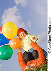 Women and child playing with balloons