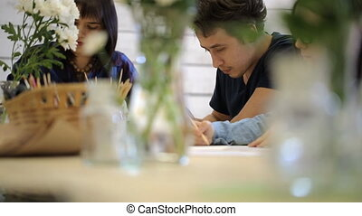 Women and man draw by pencils on sheets sitting at wooden table.