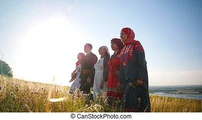 Women and man in traditional russian clothes walking in a...