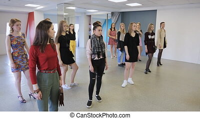 Women are getting ready for fashion show in model school.