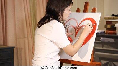 women artist painting a heart