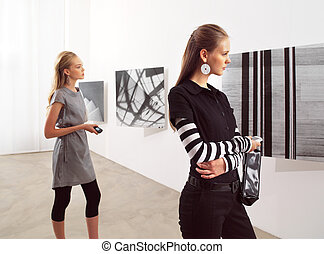women at an exhibition - women with mobile phones at an...