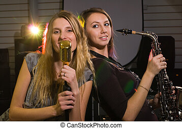 Women at concert - women with saxophone and microphone at...