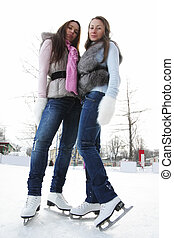 Women at ice rink low angle view - Two young brunette women...