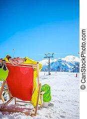 Women at mountains in winter lies on sun-lounger