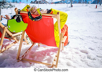 Women at mountains in winter lies on sun-lounger