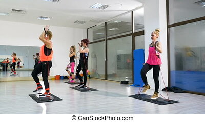 Women at the fitness club exercising for arms and legs