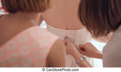 Women binding up wedding dress