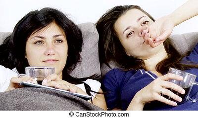 Women bored watching tv drinking coffee