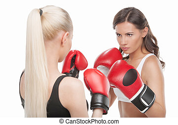 Women boxing. Two confident women boxing while standing...