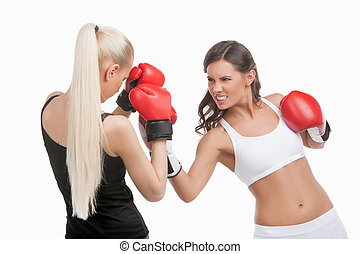 Women boxing. Two young confident women boxing while isolated on white