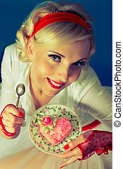 woman holds a plate with a spoonful of cake with heart