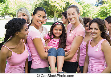 Women carrying girl during breast cancer awareness -...
