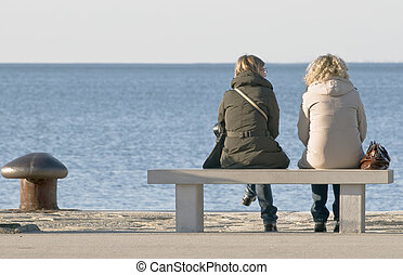 Two women talking on a bench