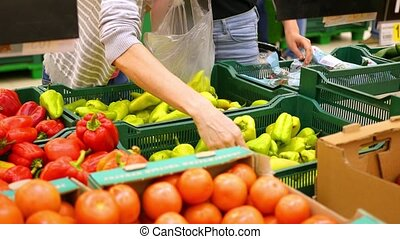 women choose vegetables at the store