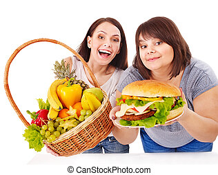 Women choosing between fruit and hamburger. Isolated.