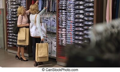 Women choosing necktie during apparel shopping - Rear view...