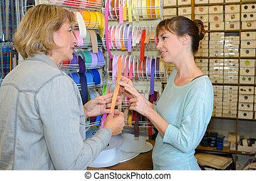 Women choosing ribbon in craft shop