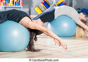 women classes in a group with gymnastic balls in the gym