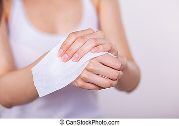 Women cleaning hands with wet wipes