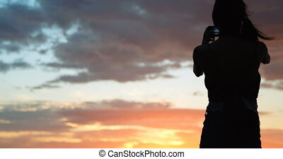 Women clicking pictures on beach during sunset 4k -...