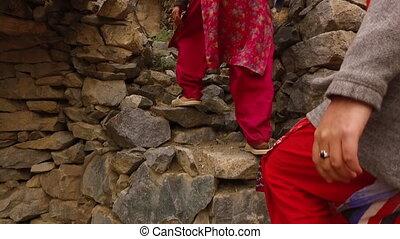Women climbing rough stone steps - Medium tracking shot of...