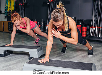 Women couple training over steppers in aerobic class -...