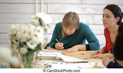 Women create drawings in art studio sitting around wooden table.