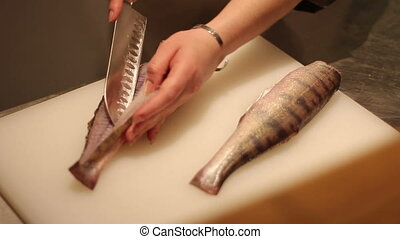women cutting fish on white Board