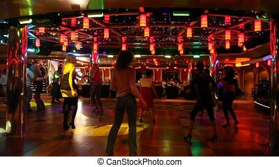 women dance on dance floor under music and multi-colored...
