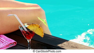 Women dangling her legs in swimming pool with cocktail on a sunny day