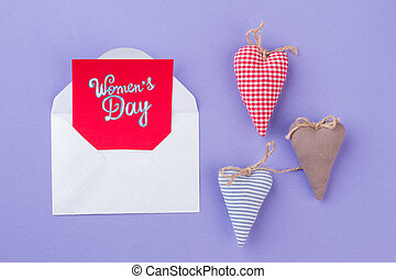 Women day concept. Handmade hearts made of textile cloth. Isolated on purple background.