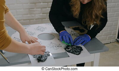 Women decorators, designers painting wooden circle...