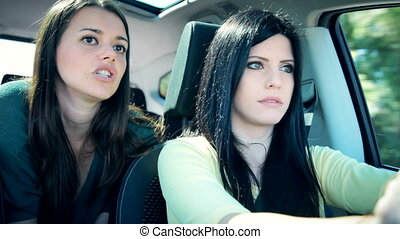 women discussing in car driving - Serious women discussing...