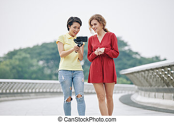 Women discussing video on smartphone