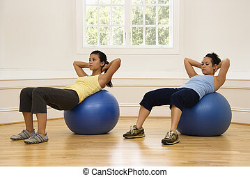 Women doing ab workout - Two young women doing ab workout on...