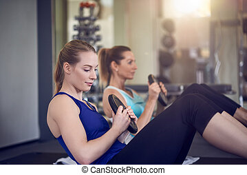 Women doing abdominal muscle exercises - Pair of young adult...
