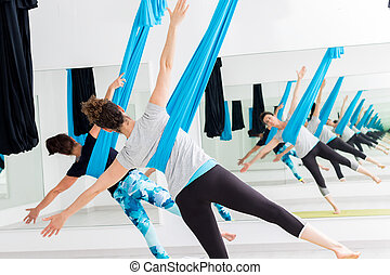 Women doing aerial yoga.