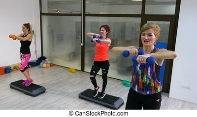 Women doing aerobics sequence with weights in hands