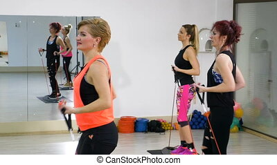 Women doing aerobics workout sequence for hands and legs at the gym