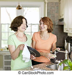 Women doing dishes in kitchen