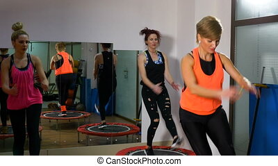 Women doing fitness session with trampoline at the gym