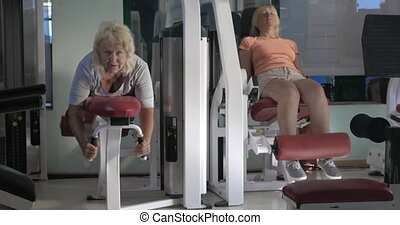 Women doing leg exercises on fitness machines